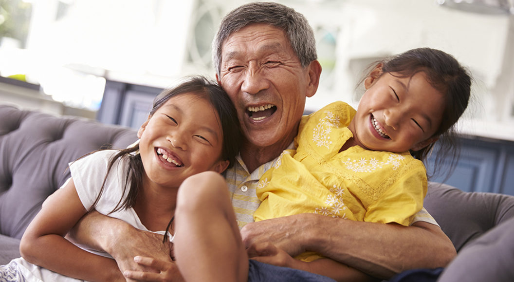Asian grand dad hugging and laughing with two grand children
